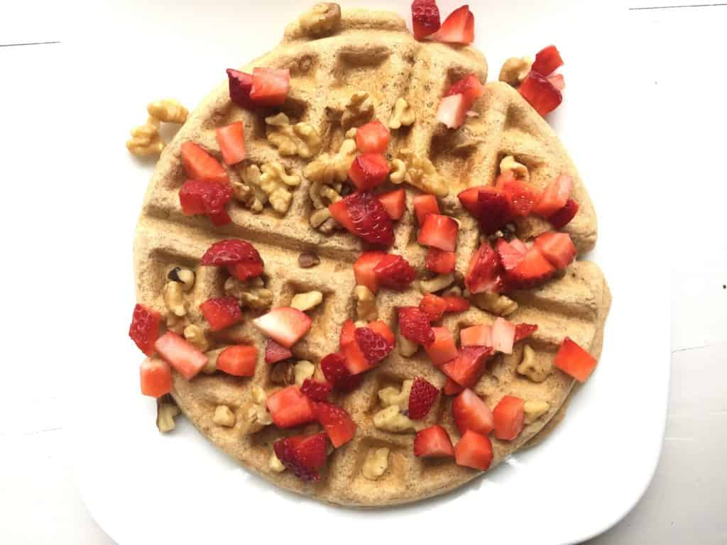 Whole grain waffle with strawberries and walnuts is perfect for a whole food, plant-based diet